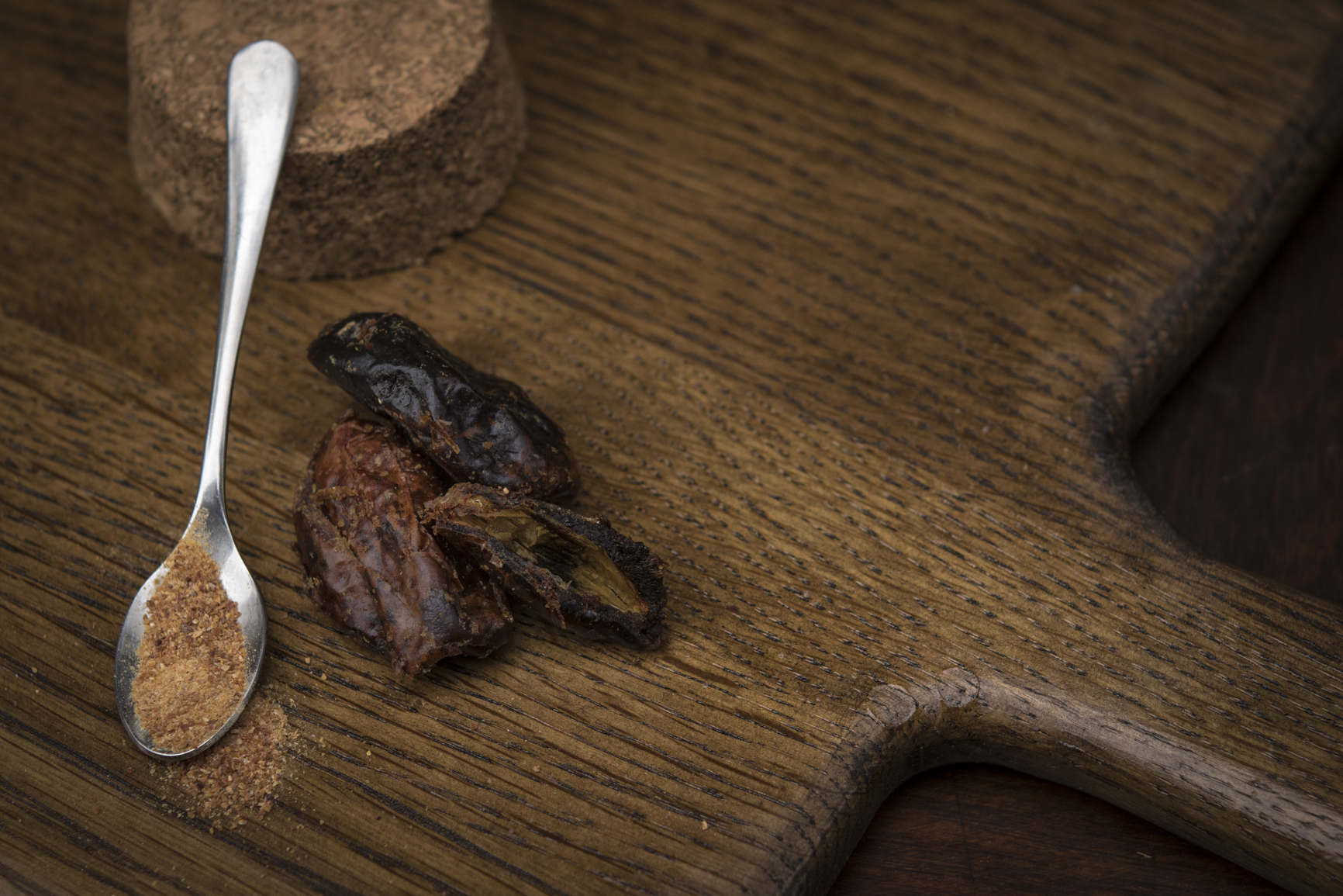 dried dates and date sugar on a teaspoon